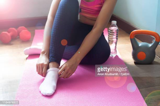 low section of woman wearing sock while sitting on floor at home on sunny day - pink sock image stock pictures, royalty-free photos & images