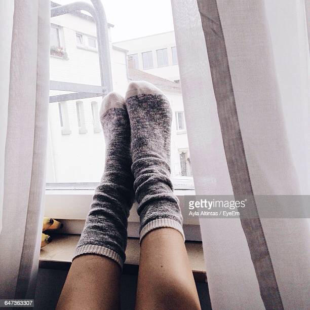 low section of woman wearing socks against window - feet up stock pictures, royalty-free photos & images