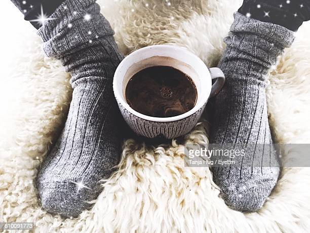 Low Section Of Woman Wearing Socks By Hot Chocolate Cup On Fur