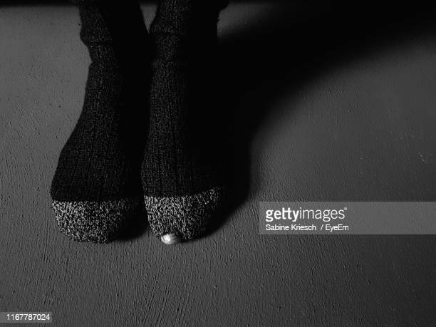 low section of woman wearing socks on floor - sabine kriesch stock-fotos und bilder