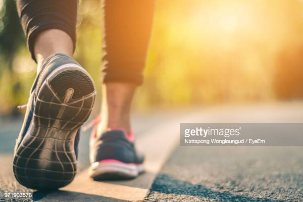 low section of woman wearing sports shoes while walking on road - low section stock pictures, royalty-free photos & images
