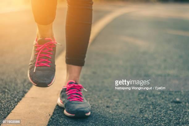 low section of woman wearing sports shoes while walking on road - sports shoe stock pictures, royalty-free photos & images