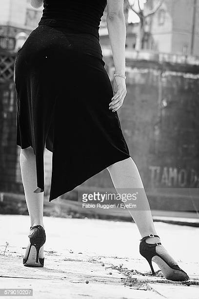 Low Section Of Woman Wearing Stiletto And Dress Dancing On Street