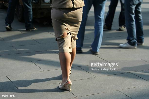 low section of woman wearing torn skirt while walking on footpath - trail of tears stock photos and pictures