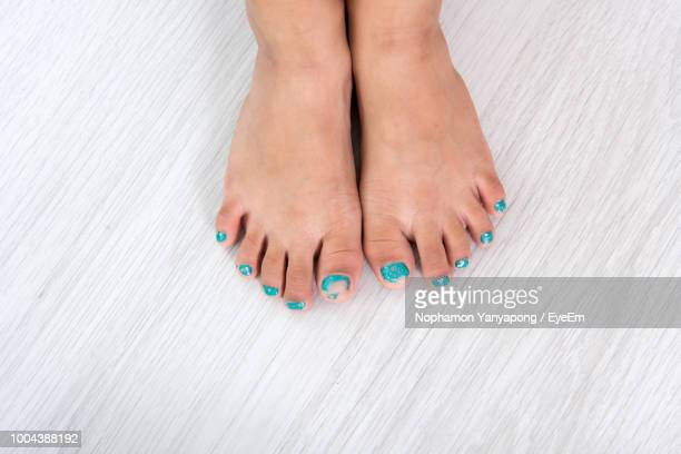 Low Section Of Woman Wearing Turquoise Nail Polish On Textured Floor At Home