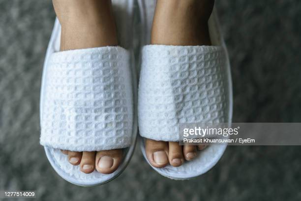 low section of woman wearing white flip-flops - open toe stock pictures, royalty-free photos & images