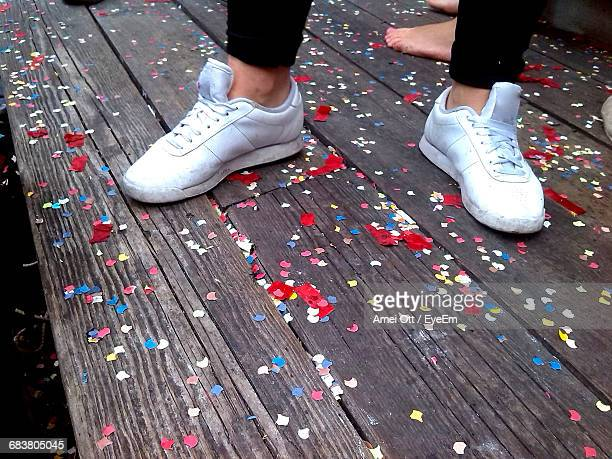 Low Section Of Woman Wearing White Shoes On Wood With Confetti