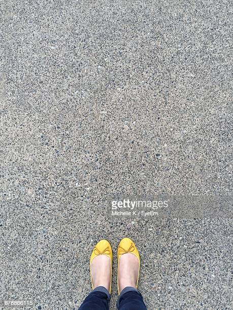 low section of woman wearing yellow shoes standing on footpath - yellow shoe stock photos and pictures