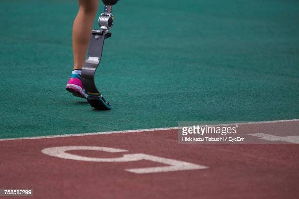 low section of woman with artificial leg running on track - assistive technology stock photos and pictures