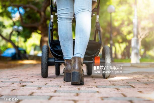 low section of woman with baby stroller while walking on footpath in park - pushchair stock pictures, royalty-free photos & images