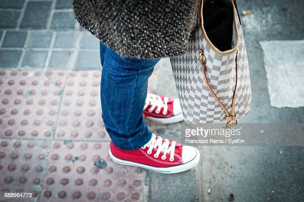 Low Section Of Woman With Bag Standing On Footpath