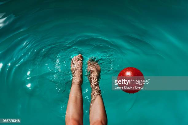 low section of woman with ball swimming in pool - asian women feet stock pictures, royalty-free photos & images