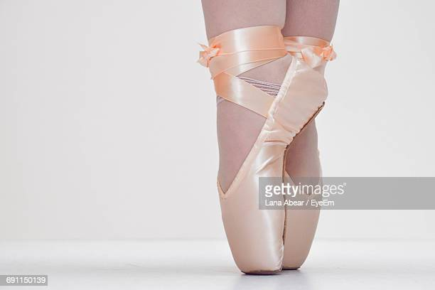 Low Section Of Woman With Ballet Shoes Against White Background
