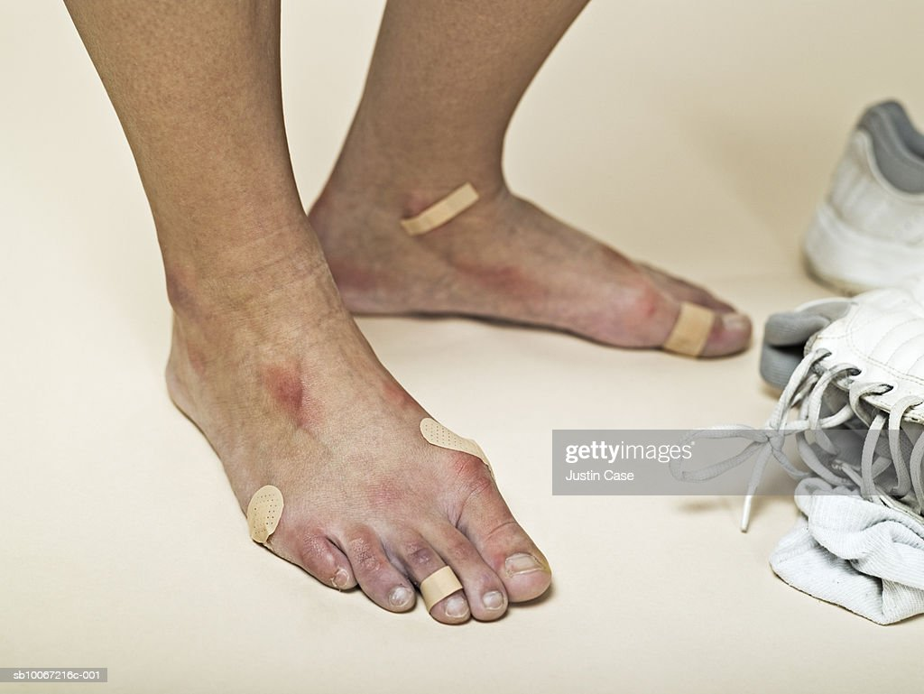 Low section of woman with bandages on feet : Stock Photo