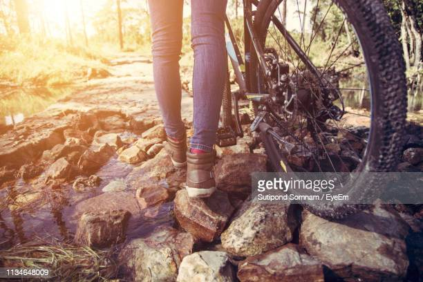 Low Section Of Woman With Bicycle Walking On Rocks