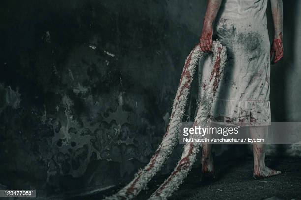 low section of woman with blood on dress holding rope while walking on floor - female torture stock pictures, royalty-free photos & images