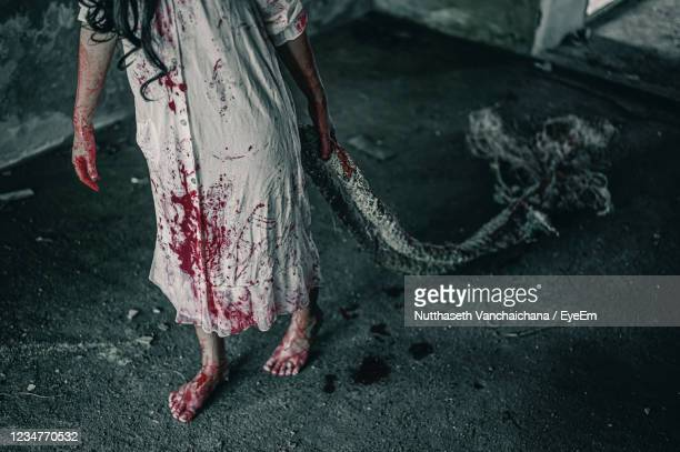 low section of woman with blood on dress walking on floor - female torture stock pictures, royalty-free photos & images