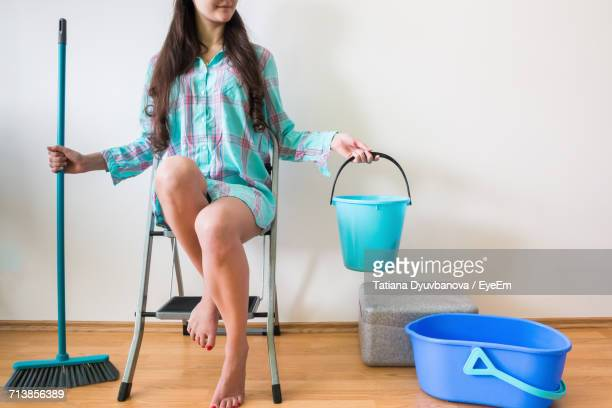 Low Section Of Woman With Bucket And Mop Sitting On Ladder At Home