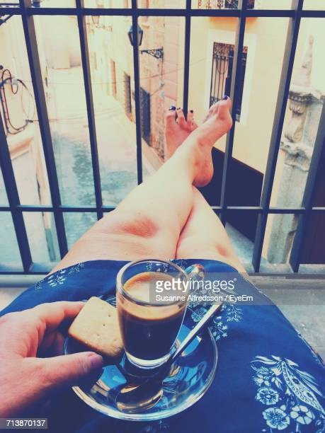 Low Section Of Woman With Coffee Cup And Cookie On Lap Relaxing By Balcony