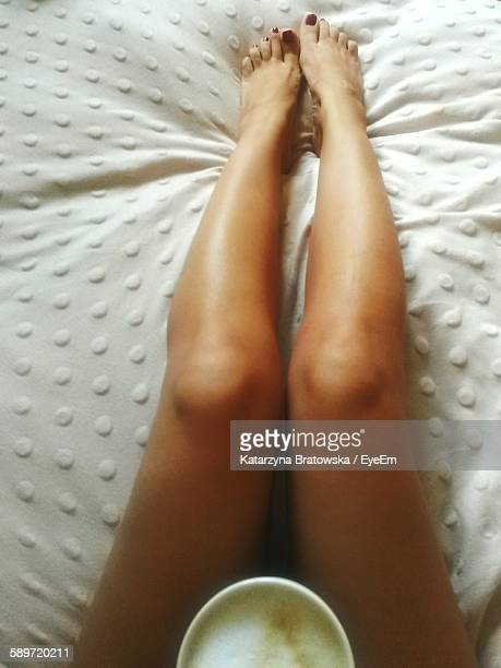 Low Section Of Woman With Coffee On Bed