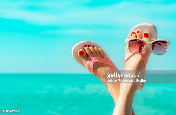 low section of woman with feet up at beach against sky - open toe stock pictures, royalty-free photos & images