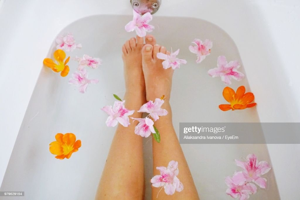 Low Section Of Woman With Flower In Bathtub : Stockfoto
