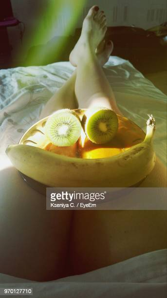 Low Section Of Woman With Fruits In Plate Relaxing On Bed At Home
