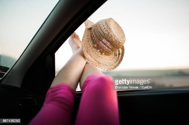 Low Section Of Woman With Hat Resting In Car Against Sky