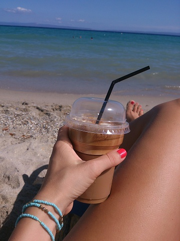 Low Section Of Woman With Iced Coffee Relaxing At Beach - gettyimageskorea