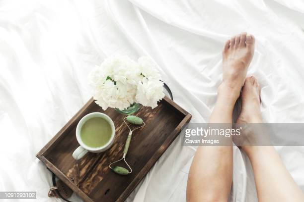 low section of woman with jade roller and matcha tea in wooden tray on bed - massage rooms photos et images de collection