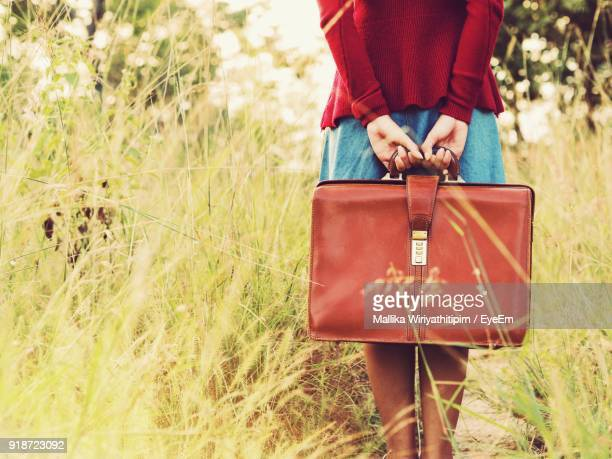 Low Section Of Woman With Leather Bag Standing On Grassy Field
