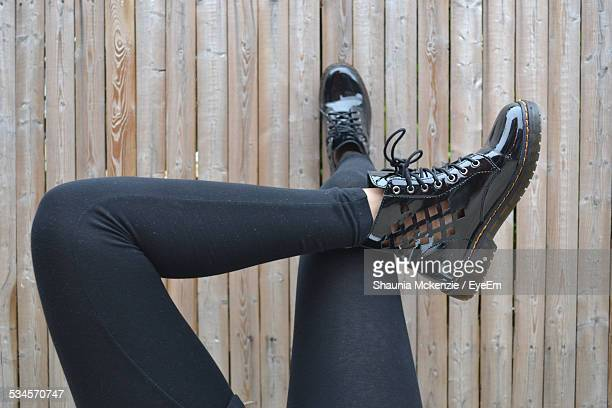 Low Section Of Woman With Legs Crossed At Knee Against Wooden Fence