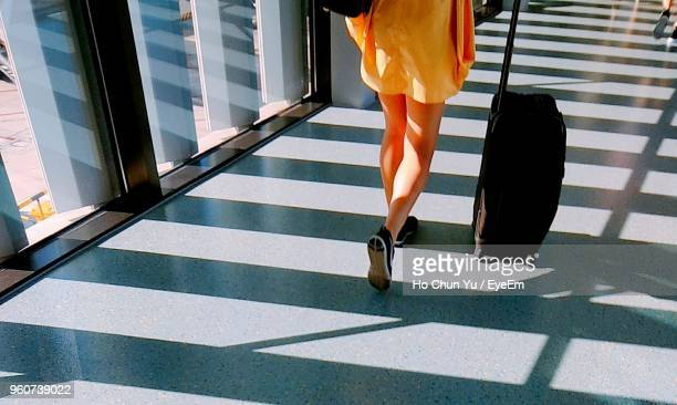 low section of woman with luggage walking at airport - low section stock pictures, royalty-free photos & images