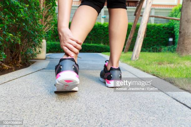 Low Section Of Woman With Pain In Ankle At Park