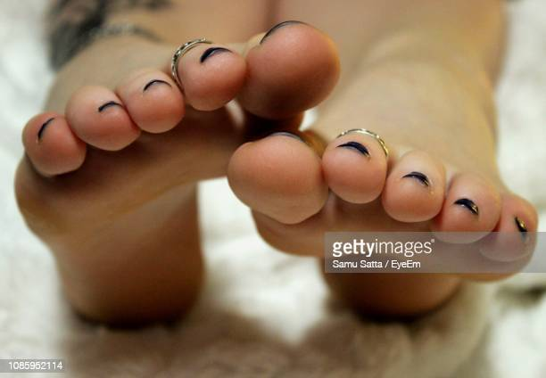 Low Section Of Woman With Painted Toenails On Bed