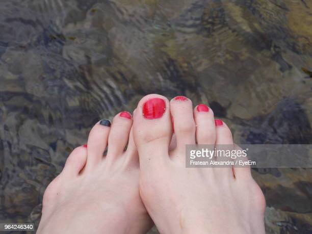 Low Section Of Woman With Painted Toenails Over Lake