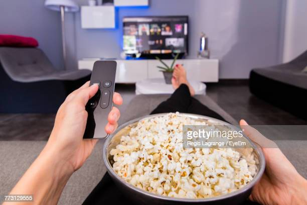 Low Section Of Woman With Popcorns Watching Television While Sitting On Sofa At Home
