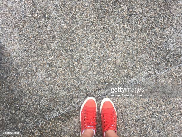 Low Section Of Woman With Red Canvas Shoes On Footpath