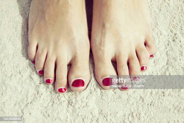 low section of woman with red nail polish standing on sand - toe stock pictures, royalty-free photos & images