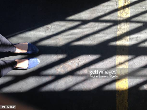 low section of woman with shadow standing on floor - human leg stock photos and pictures