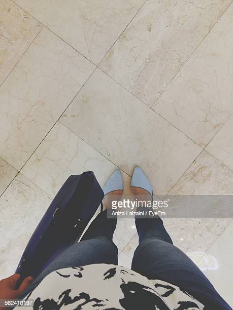 Low Section Of Woman With Shopping Bag Standing On Tiled Floor