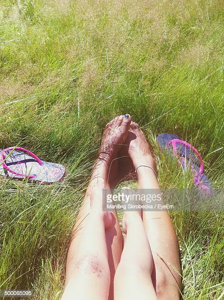 Low section of woman with son relaxing on grass