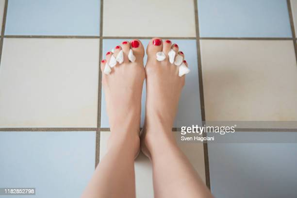 low section of woman with tissues between painted toe nails on tiled floor - pedicure stock pictures, royalty-free photos & images