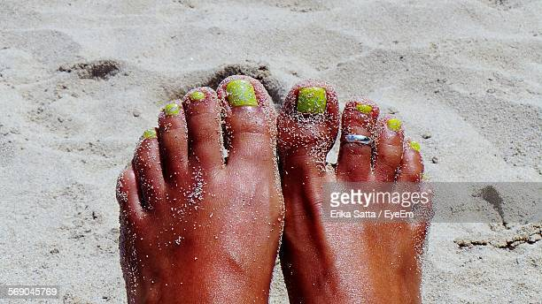 low section of woman with toe ring resting on sand at beach - toe stock pictures, royalty-free photos & images