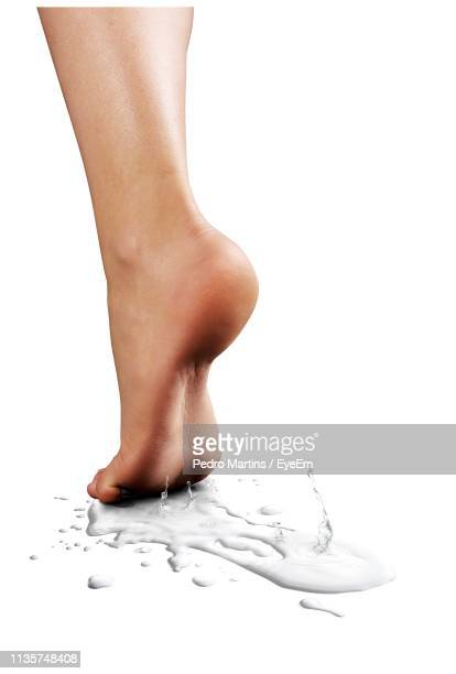 low section of woman with water footprint against white background - 部分 ストックフォトと画像