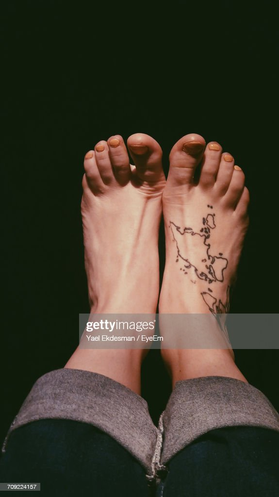 Low section of woman with world map tattoo on foot at night stock low section of woman with world map tattoo on foot at night stock photo gumiabroncs Choice Image