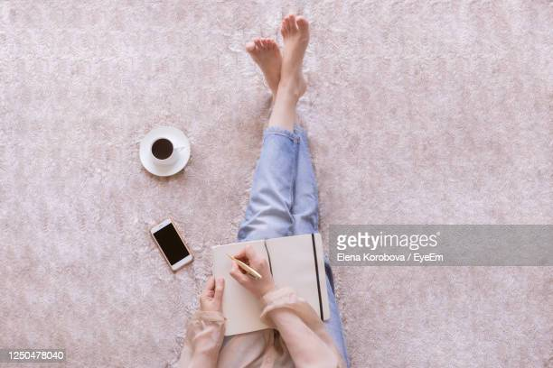 low section of woman writing in diary while sitting on carpet - carpet stock pictures, royalty-free photos & images