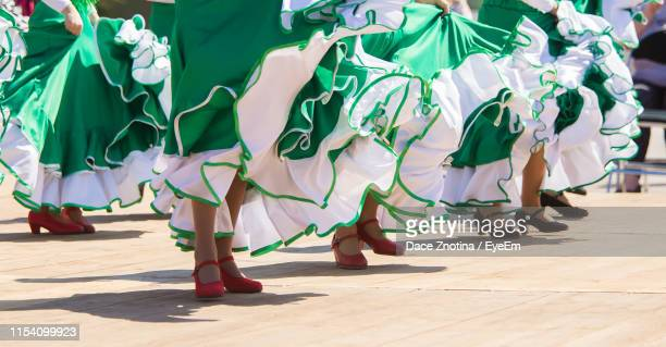 low section of women dancing on footpath during sunny day - riga stock pictures, royalty-free photos & images