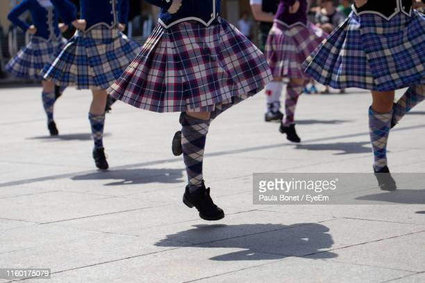 low section of women dancing on footpath - piper stock photos and pictures