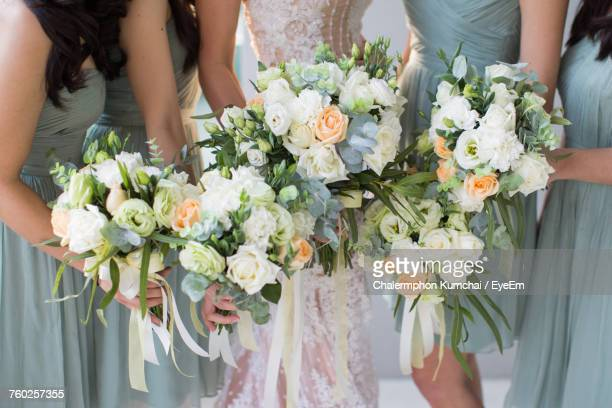 low section of women holding flower bouquets - bridesmaid stock pictures, royalty-free photos & images